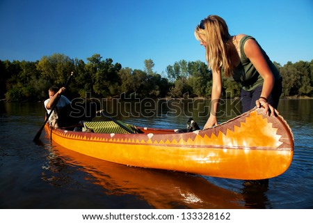 Young couple enjoying a trip in a canoe - stock photo