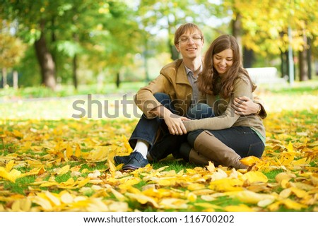 Young couple enjoying bright and warm autumn day in park or forest - stock photo