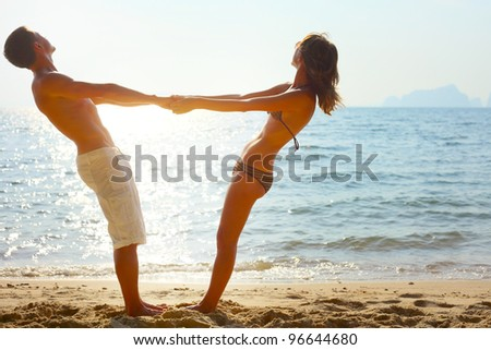 Young couple enjoying each other on a tropical beach at sunset - stock photo