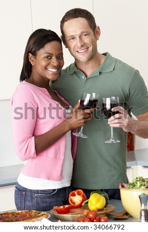 Young Couple Enjoying Glass Of Wine In Kitchen - stock photo