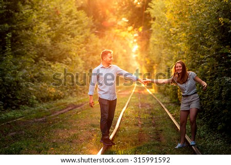 young couple enjoying having fun and on the tram rails in city park. - stock photo