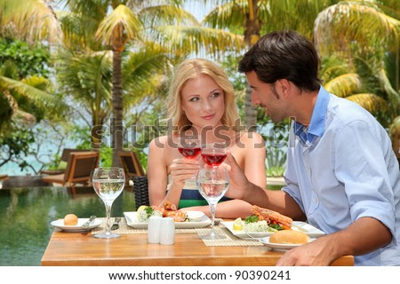 Young couple enjoying lunch in resort restaurant - stock photo