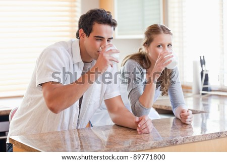 Young couple enjoying some milk in the kitchen - stock photo