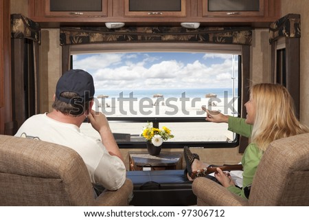 Young Couple Enjoying the Beach View From Their 5th Wheel RV. - stock photo