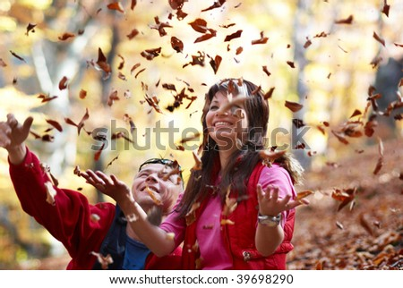 Young couple enjoying the falling leaves in the autumn park - stock photo