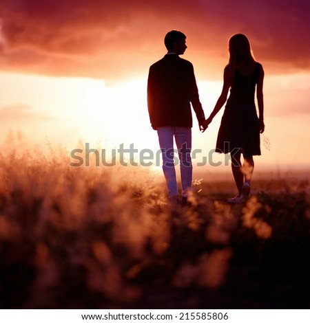 Young couple enjoying the sunset in the meadow - stock photo