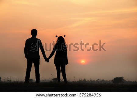 Young couple enjoying the sunset silhouette style. - stock photo
