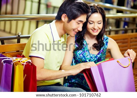 Young couple enjoying their purchases after a long shopping day - stock photo