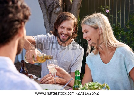 young couple enjoying white wine outdoors at garden party - stock photo
