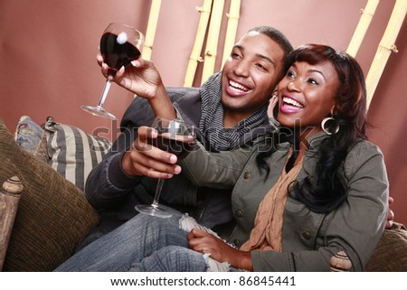Young couple enjoys red wine at the bamboo foyer - stock photo