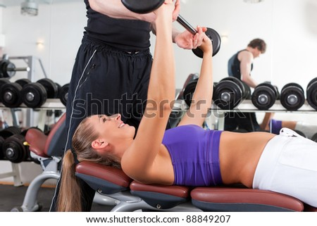 Young couple exercising in gym with weights; the man seems to be the personal trainer - stock photo