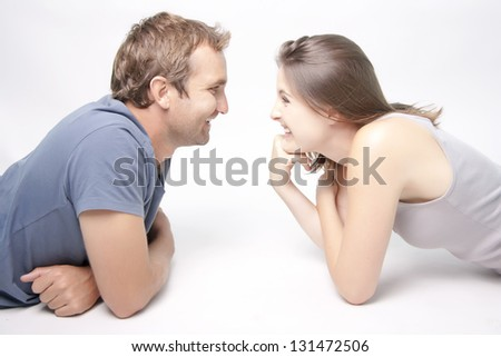 Young Couple facing each other smiling playfully - stock photo