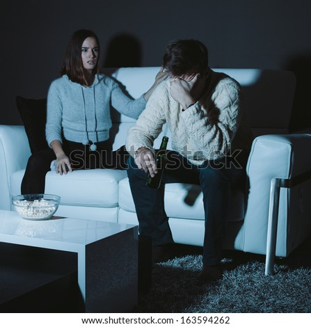Young couple fighting at home while watching TV - stock photo