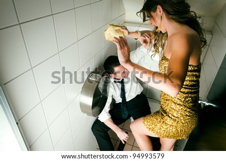 Young couple fighting on a party in the toilette, he is obviously drunk - stock photo