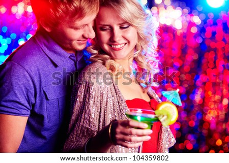 Young couple flirting at party against sparkling background - stock photo