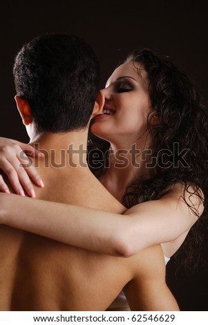 young couple flirting with each other, while the woman is biting the man's ear - stock photo
