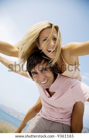 young couple fooling around on the beach - stock photo