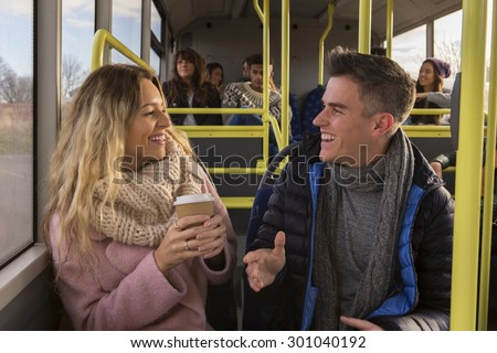 Young couple/friends chatting on a bus together. There are other people on the bus in the background. - stock photo