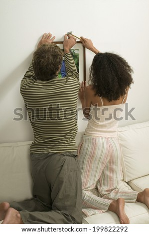 Young couple hanging up picture - stock photo
