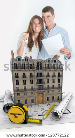 Young couple happily holding a contract and a bunch of keys with a building and blueprints - stock photo
