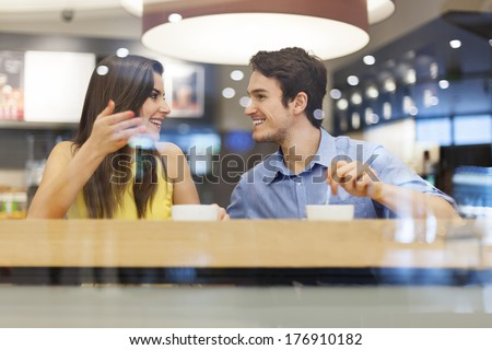 Young couple have interesting discussion in cafe  - stock photo