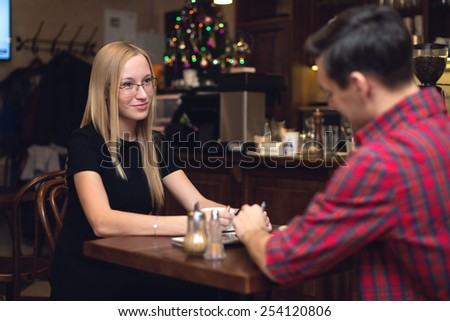 Young couple having a date in a cafe drinking coffee staring at each other. - stock photo