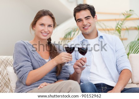 Young couple having a glass of red wine in their living room - stock photo