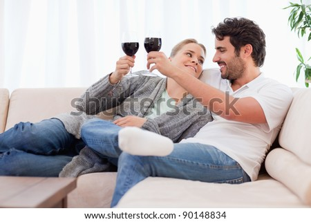 Young couple having a glass of wine in their living room - stock photo