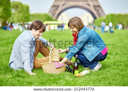 Young couple having a picnic near the Eiffel tower in Paris - stock photo