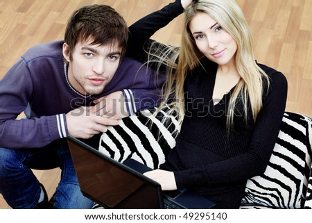 Young couple having a rest with a laptop at home.