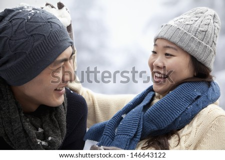 Young Couple Having a Snowball Fight - stock photo