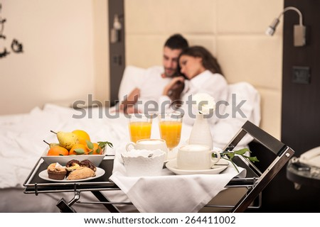Young couple having breakfast in luxury hotel room. Focus on tray. - stock photo