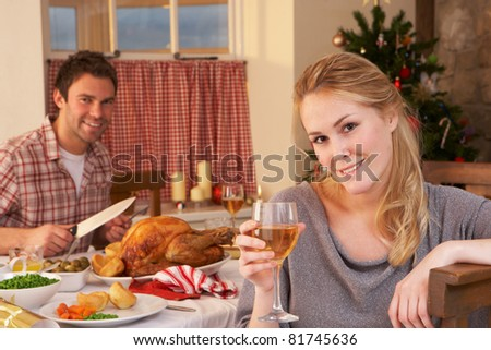 Young couple having Christmas dinner - stock photo