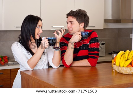 Young couple having conversation and drinking coffee in the morning in their kitchen