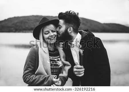 Young couple having fun and celebrating life, holding sprinkles and kissing  - stock photo