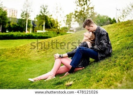 Young couple having fun and hugging in the park. Engagement session. Dressed in black leather jackets. Girl wears glasses