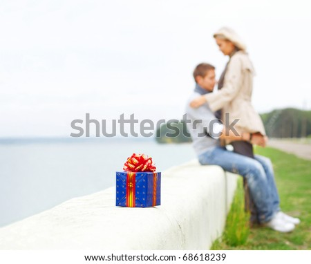 Young couple having fun at beach. They smiling. Gift-box on a foreground - stock photo