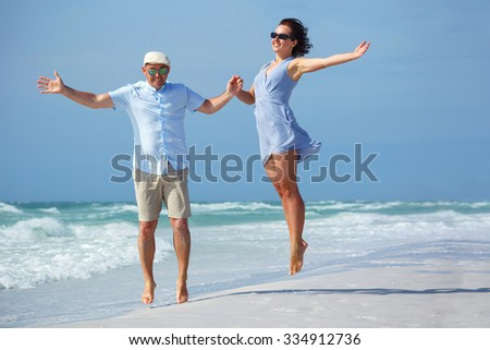 Young couple having fun at tropical beach during summer vacation, Siesta Key beach, Florida  - stock photo