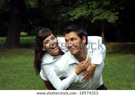 Young couple having fun in a park - stock photo