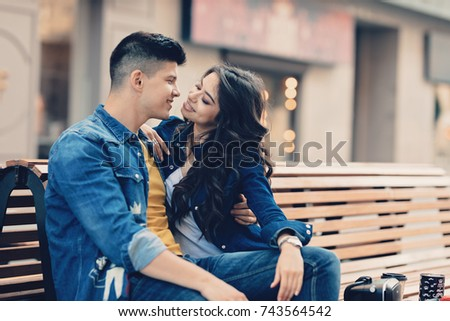 Young couple having fun in the city. Smiling couple in love drinking coffee on the street.Excited happy couple hugging on the city street.