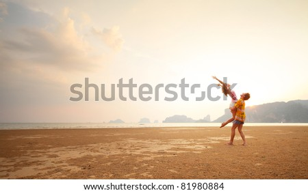Young couple having fun on a sandy coast - stock photo