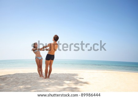 Young couple having fun on a white sand by sea on blue clear sky background - stock photo