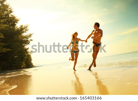 Young couple having fun on the tropical beach at sunny day - stock photo