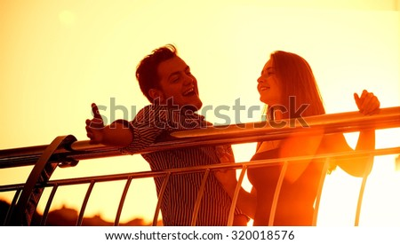 Young couple having fun, singing something, standing on a bridge, against the sunset. - stock photo