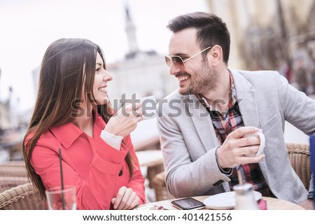 Young couple having fun while sitting together in a city cafe.Couple having a cup of coffee on a date. - stock photo