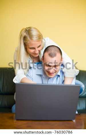 Young couple having fun with laptop at home. - stock photo