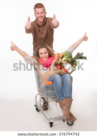 Young couple having fun with shopping cart over white background. Woman showing thumb-ups and holding products. - stock photo