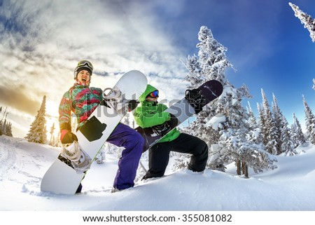 Young couple having fun with snowboards at sunset time. Playing on snowboards like on guitar. Sheregesh resort, Siberia, Russia. - stock photo