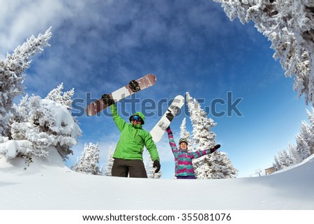 Young couple having fun with snowboards. Sheregesh resort, Siberia, Russia. - stock photo