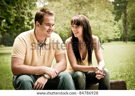 Young couple having great time - sitting on bench outdoors - stock photo